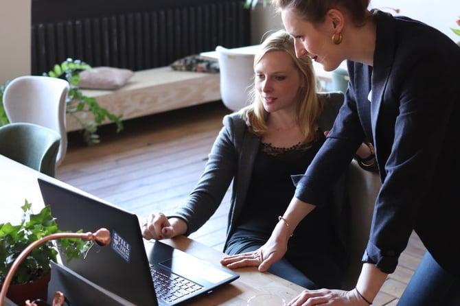 Deux femmes se tenant devant un ordinateur